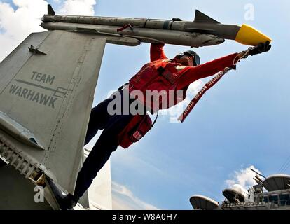 U.S. Navy Petty Officer 2nd Class Stephen Bailey caps a missile attached to an F/A-18C Hornet aboard the aircraft carrier USS John C. Stennis in the South China Sea on Sept. 2, 2011. - Stock Photo
