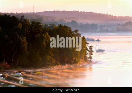Stockholm Archipelago, red holiday stuga cottage on island, Baltic Sea view, misty morning sunrise turns sky and hills pink, authentic color, Sweden - Stock Photo