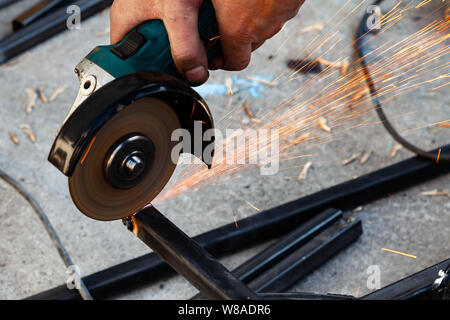 Close-up view strong man master without gloves on arms, performs metal cutting with an angle grinder in the garage workshop, blue and orange sparks fl - Stock Photo