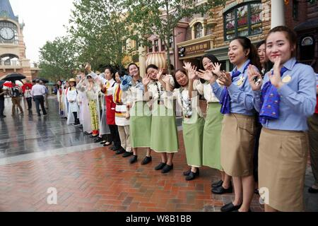 Employees wave to tourists in the Shanghai Disneyland at the Shanghai Disney Resort in Pudong, Shanghai, China, 16 June 2016.   In a rain-dampened cer - Stock Photo