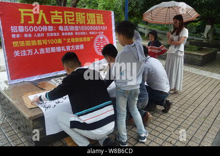 Chinese applicants write a slogan 'Mother-in-law is mother' during a recruitment event for 5,000 best men for a grand wedding featuring 10,000 best me - Stock Photo