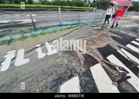 Pedestrians walk on a zebra crossing featuring a 3D painting of a zebra in Xuhui District, Shanghai, China, 8 May 2016. - Stock Photo
