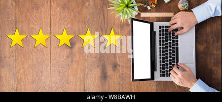 An Elevated View Of Five Star Rating With Receptionist Using A Laptop - Stock Photo