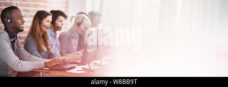 Young Customer Service Executives Using Earphones Working In Call Center - Stock Photo