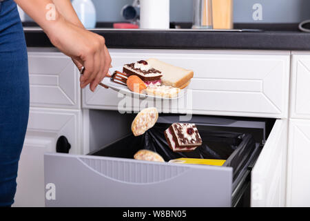 Close-up Of A Woman's Hand Throwing Food In Trash Bin - Stock Photo