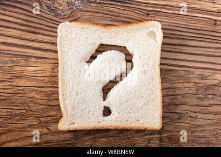 Slice Of Bread With An Question Mark Sign On Wooden Desk - Stock Photo