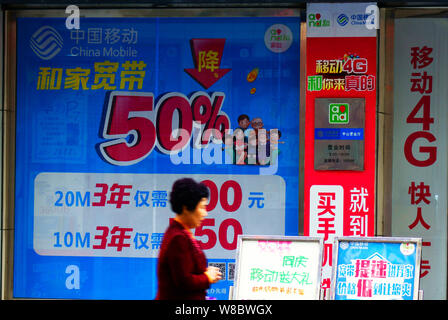 --FILE--A pedestrian walks past advertisement for 4G and broadband services at a branch of China Mobile in Yichang city, central China's Hubei provinc - Stock Photo