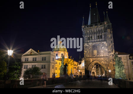 People at the Charles Bridge (Karluv most) and lit St. Francis of Assissi Church and Old Town Bridge Tower at the Old Town in Prague in the evening. - Stock Photo