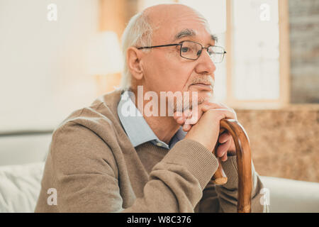 Neat partly-bald old man thoughtfully relying on the wooden stick - Stock Photo