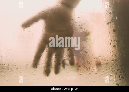 Human Hand pressed against a window with Drops Of Rain on it. Hand touching clear glass with water droplet. Natural Pattern of raindrops isolated from - Stock Photo