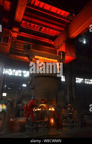 --FILE--Chinese workers survey the production of steel around a furnace containing molten steel at a plant of Dongbei Special steel Group Co., Ltd. in
