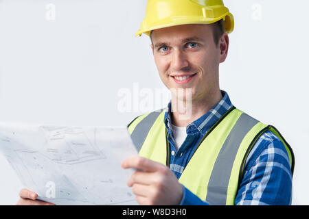 Studio Portrait Of Builder Architect Looking At Plans Against White Background - Stock Photo
