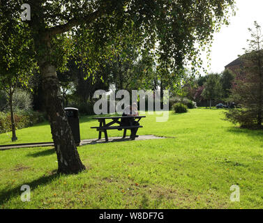 Male deep in thought thinking while seated on a picnic bench table in a park area on a warm sunny day in England UK. photo DON TONGE - Stock Photo