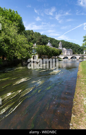 Brantome en Perigord, France. The River Dronne, with the Pont Coude, Hotel Le Moulin de l'Abbaye and the Abbey of Brantome in the background. - Stock Photo