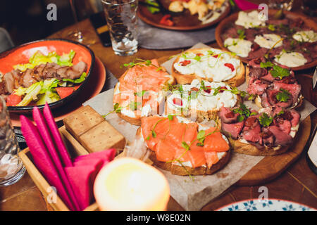 Appetizers table with italian antipasti snacks and wine in glasses. Brushetta or authentic traditional spanish tapas set, cheese variety board over - Stock Photo