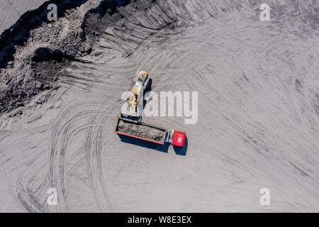 Aerial photo of excavator pours sand into the truck. On the construction site top view. Shooting from the drone. - Stock Photo