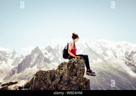 Young female traveller sitting on the edge of rocks. High mountains in background. Woman backpacking. Hiking adventure. Active lifestyle. Explore conc - Stock Photo