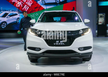 --FILE--A Chinese employee walks past a Honda VEZEL during the 12th China (Guangzhou) International Automobile Exhibition, also known as Auto Guangzho - Stock Photo