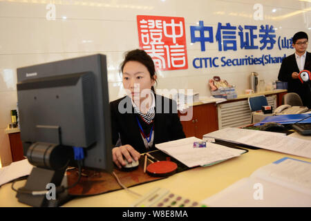 --FILE--A Chinese employee works at a branch of CITIC Securities in Qingdao city, east China's Shandong province, 24 March 2015.    Citic Securities s - Stock Photo
