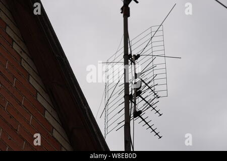 TV antenna on the roof of house - Stock Photo