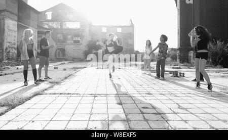 Energetic young people hip hop street dancers performing their routine in an urban square backlit by a bright sun flare over high-rise buildings - Stock Photo