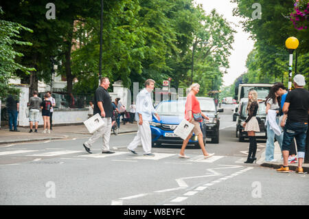 Tourists following in the footsteps of the Beatles on the pedestrian crossing in front of the recording studios at Abbey Road. - Stock Photo