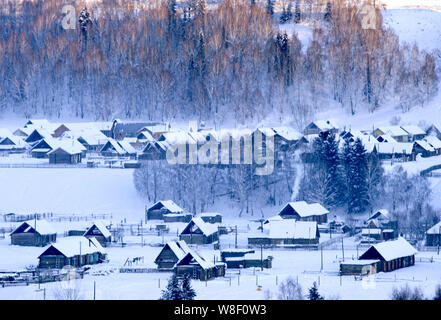 Landscape of houses near the Kanas Lake in the snow in Altay Prefecture, southwest China's Xinjiang Autonomous Region, 28 December 2008. - Stock Photo