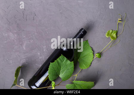 A bottle of red wine next to ripe grapes with leaves on a gray background. Top view, flat lay, copy space - Stock Photo