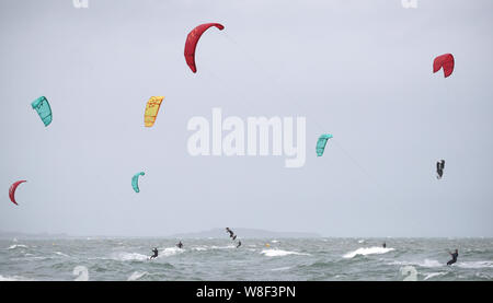 Kite surfers enjoy the strong winds off of Branksome Chine, near Poole in Dorset. Warnings for rain and wind came into force across nearly all of the UK today. - Stock Photo