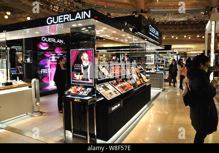 --FILE--Tourists from mainland China walk past a counter of Guerlain at the Galeries Lafayette shopping mall in Paris, France, 13 January 2015.   The - Stock Photo