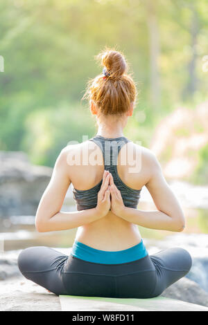 Asian young woman practicing yoga near waterfall - Stock Photo