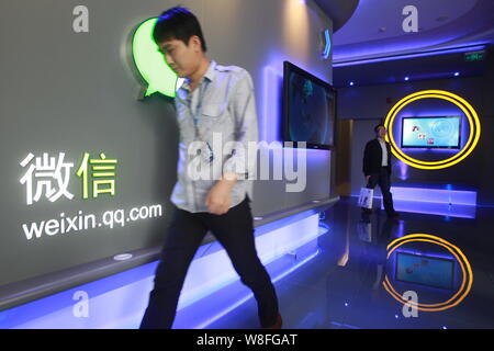 --FILE--A Chinese employee walks past a logo of Weixin.com (Wechat) at the headquarters of Tecent in Shenzhen city, south China's Guangdong province, - Stock Photo