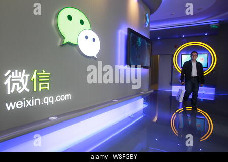 --FILE--A Chinese employee walks past a logo of Weixin.com (Wechat) at the headquarters of Tecent in Shenzhen city, southeast China's Guangdong provin - Stock Photo
