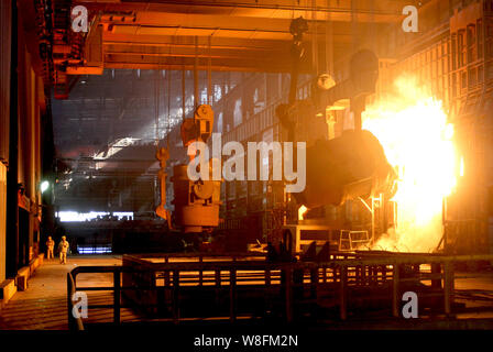 --FILE--Chinese workers survey the production of steel next to a furnace containing molten steel at a steel plant in Huaian city, east China's Jiangsu