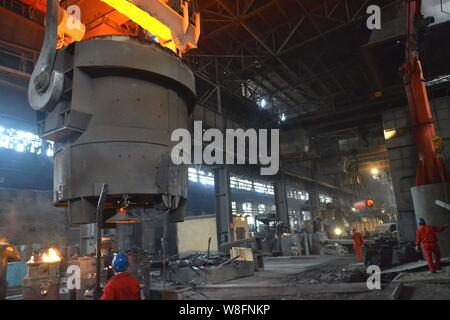--FILE--Chinese workers survey the production of steel next to a furnace containing molten steel at a plant of Dongbei Special Steel Group Co., Ltd. i