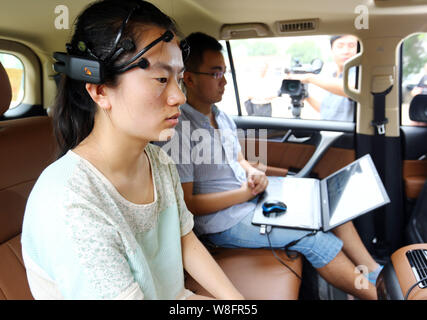 A team member, left, wearing a headset with 16 sensors that sends impulses from the user's brain to the car's processing system, orders a mind-control - Stock Photo