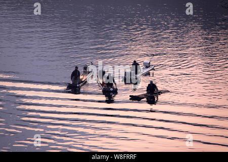 --FILE--Chinese fishermen are fishing on bamboo rafts on the Yulong River in Yangshuo county, Guilin city, south China's Guangxi Zhuang Autonomous Reg - Stock Photo
