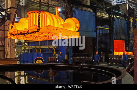 --FILE--Chinese workers survey the production of steel next to a furnace at a plant of Citic Heavy Industries Co., Ltd. in Luoyang city, central China