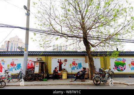 Bicycle repairmen talk on the street in front of the construction site of the Fengsheng International Finance Center which is said to be the headquart - Stock Photo