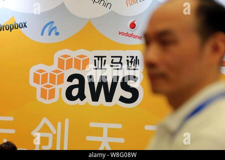 --FILE--A Chinese employee walks past the stand of AWS (Amazon Web Services) during the 13th China Digital Entertainment Expo, also known as ChinaJoy - Stock Photo