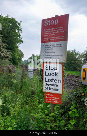 Train warning signs at an unmanned country railway line level crossing in rural Nursling, Redbridge, Test Valley, Southampton, Hampshire - Stock Photo