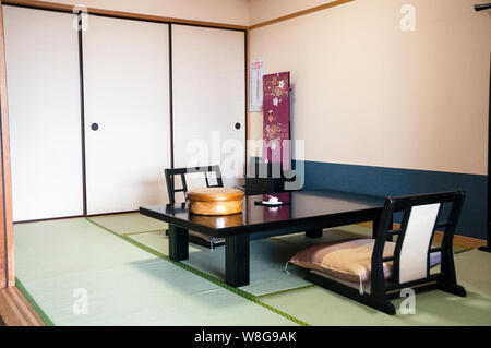 Traditional Japanese tea service in hotel room in Hakone, Japan includes zabuton cushions and a Chabudai table with zaisu, or legless chair. - Stock Photo