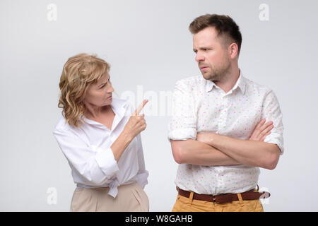 Business woman pointing at her coworker blaming him - Stock Photo