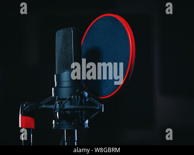 Microphone on black background in recording studio. Music, concert concept. - Stock Photo