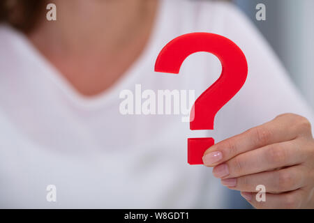 Close-up Of A Businesswoman's Hand Holding Red Question Mark Sign - Stock Photo