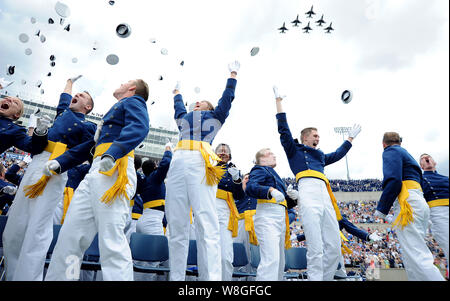 Members of the U.S. Air Force Academy Class of 2015 toss their hats in celebration as the Thunderbirds roar over Falcon Stadium in Colorado Springs, C - Stock Photo