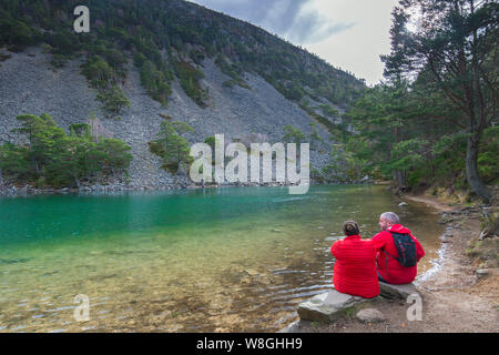 Tourists on lake bank of An Lochan Uaine in the Glenmore Forest Park, Cairngorms National Park near Aviemore, Badenoch and Strathspey, Scotland, UK - Stock Photo