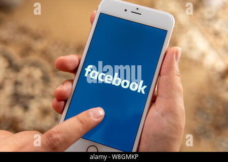 Female hand with Apple phone with logo of social media Facebook on the screen. Social media icon. Can be used as illustration for news media concept - Stock Photo