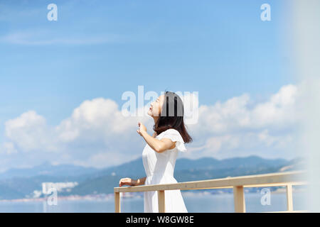 side view of a young asian woman standing by sea looking up at blue sky - Stock Photo