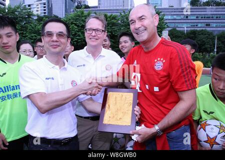 Former German soccer star Raimond Aumann, right, poses with his handprint during a fan meeting event in Guangzhou city, south China's Guangdong provin - Stock Photo